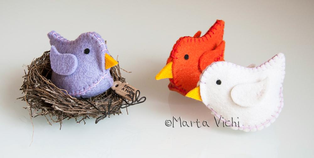 Uccellino lilla con zampine, uccellini arancione e bianco panna.