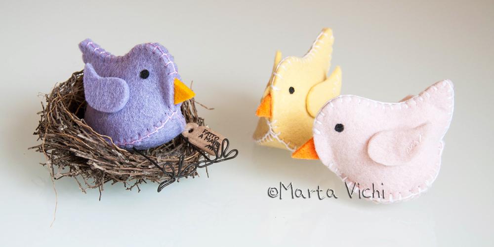 Uccellino viola con zampine, uccellino giallo e rosa.